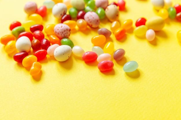 Vrolijk pasen concept. voorbereiding op vakantie. pasen snoep chocolade-eieren en jellybean snoep geïsoleerd op trendy geel. eenvoudig minimalisme plat lag bovenaanzicht kopie ruimte.