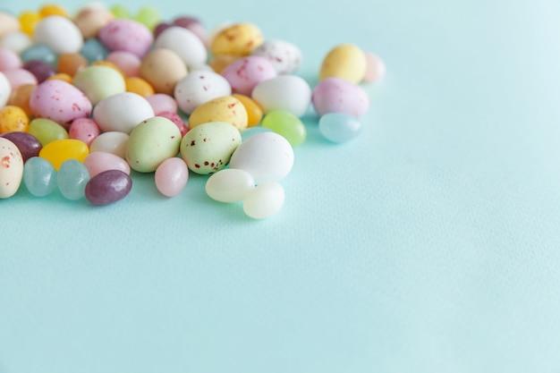 Vrolijk pasen concept. voorbereiding op vakantie. pasen snoep chocolade-eieren en jellybean snoep geïsoleerd op trendy pastel blauw. eenvoudig minimalisme plat lag bovenaanzicht kopie ruimte.