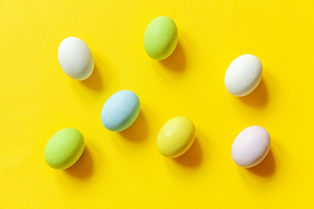 Vrolijk pasen concept. voorbereiding op vakantie. pasen snoep chocolade-eieren kleurrijke pastel snoepjes en bunny speelgoed geïsoleerd op trendy geel. eenvoudig minimalisme plat lag bovenaanzicht kopie ruimte.