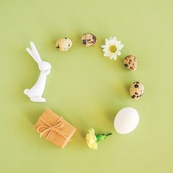Vrolijk pasen feestelijk cirkelframe. pasen-lay-out die van diverse eieren, konijntjesbeeldje, bloemen en ambachtgift wordt gemaakt op groene achtergrond met exemplaarruimte