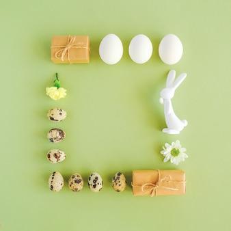 Vrolijk pasen feestelijk vierkant frame. pasen-lay-out die van diverse eieren, konijntjesbeeldje, bloemen en ambachtgift wordt gemaakt op groene achtergrond met exemplaarruimte