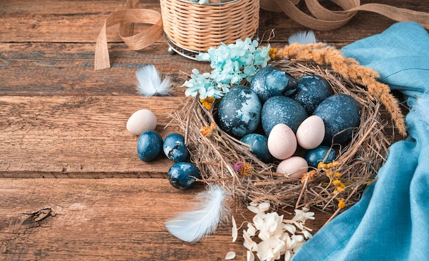 Vrolijk pasen, feestelijke achtergrond met eieren in een nest op een houten achtergrond.