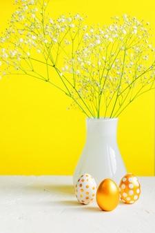 Vrolijk pasen interieur. drie gouden eieren en witte bloeiende gipskruid op heldere gele achtergrond. feestelijk vakantiestilleven