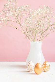 Vrolijk pasen interieur. drie gouden eieren en witte bloeiende gipskruid op roze achtergrond. teder gezellig stilleven.