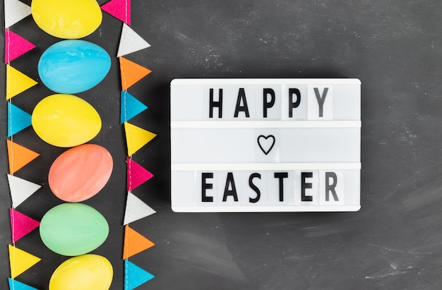 Vrolijk pasen-letters op wit bord met kleurrijke beschilderde eieren en viltslinger op krijtbord