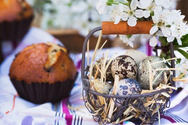 Vrolijk pasen - mand met eieren en cupcakes op de achtergrond van kersenbloesems