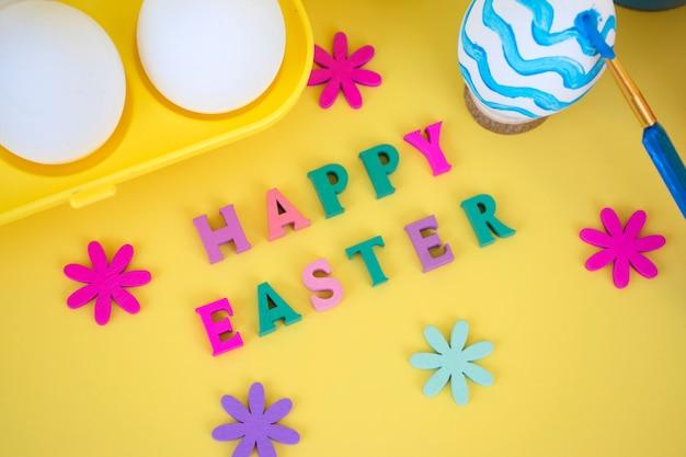 Vrolijk pasen-woord gemaakt van kleurrijke letters met houten bloemen, eieren in geel eierrekje en penseel paitning ei in blauwe golven op geel
