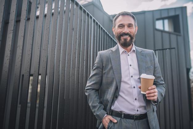 Vrolijk persoon. gelukkig volwassen bebaarde man in stijlvol pak staande met glas koffie buiten in de buurt van kantoorgebouw