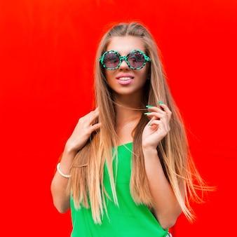 Vrolijk portret van mooie vrouw lachend in zonnebril in de buurt van een felrode muur
