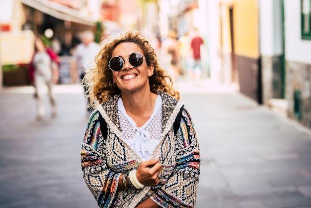 Vrolijk portret van trendy, mooie blanke dame die lacht en wandelt in de stad met een lentejasje