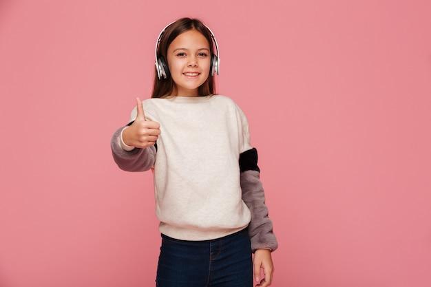 Vrolijk positief meisje in hoofdtelefoons die omhoog geïsoleerde duim tonen