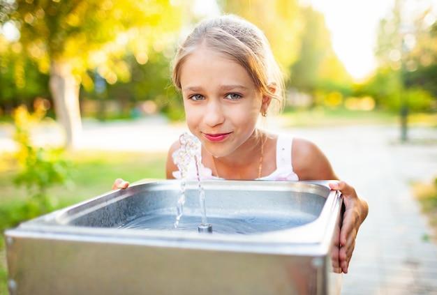 Vrolijk prachtig meisje drinkt koel vers water uit een kleine fontein in een zomers warm zonnig park op een langverwachte vakantie