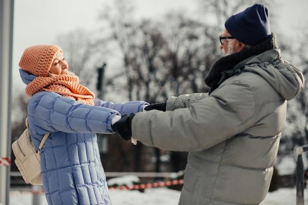 Vrolijk romantisch paar oude mensen in winterkleren die buiten ontspannen en dansen