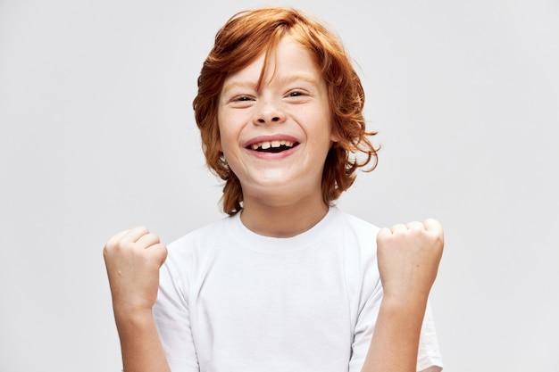 Vrolijk roodharig kind met wit t-shirt