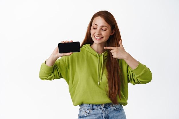 Vrolijk roodharig meisje dat naar de horizontale mobiele telefoon-app wijst, de online winkel op het scherm laat zien en glimlacht of videogame op wit