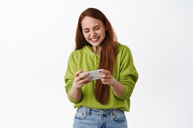 Vrolijk roodharig meisje dat op de mobiele telefoon van een videogame speelt, grappige video's op een smartphone bekijkt en lacht, op wit staat