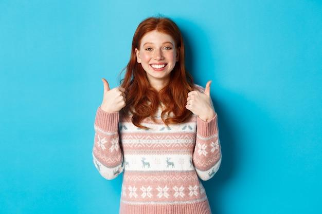 Vrolijk roodharig meisje in de wintersweater met duimen omhoog, eens en leuk, haar steun tonen en glimlachen, tevreden staan tegen een blauwe achtergrond.