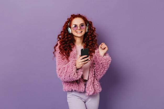 Vrolijk roodharig meisje in roze eco-jas en lichte broek glimlachen. vrouw in blauwe koptelefoon houdt zwarte smartphone.