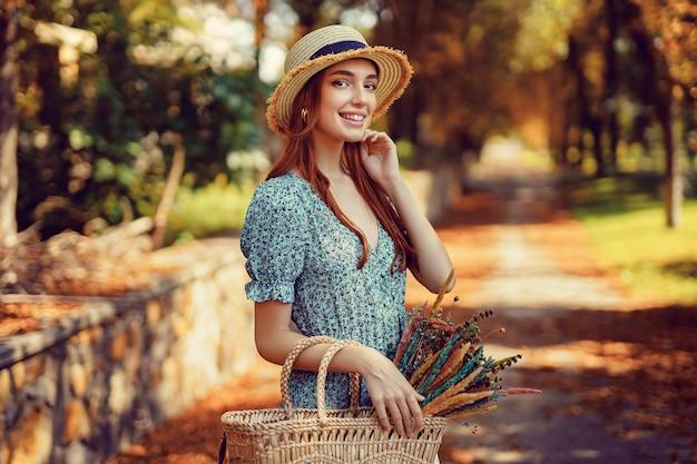 Vrolijk roodharig meisje loopt alleen in het herfstpark op een zonnige warme dag terwijl ze in de zomer een handtas vasthoudt