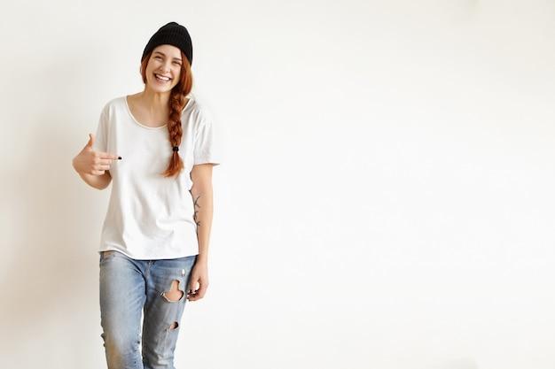 Vrolijk roodharig meisje met gevlochten kapsel met zwarte hoed en haveloze spijkerbroek, wijzende vinger naar haar witte oversized t-shirt