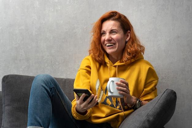 Vrolijk roodharig meisje met kop en telefoon in handen op bank. chatten met vrienden.