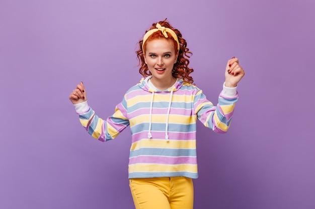 Vrolijk roodharige tienermeisje in kleurrijke outfit dansen op lila muur