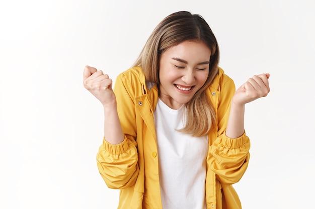 Vrolijk schattig aziatisch blond meisje voel dolblij geluk zoet succes dansen ogen dicht glimlachen breed knijpen handen triomferen vieren overwinning uitstekend nieuws perfecte score doel bereiken