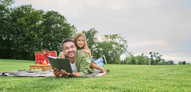 Vrolijk schattig klein meisje dat tijd doorbrengt met haar vader die een boek leest terwijl ze picknickt in de
