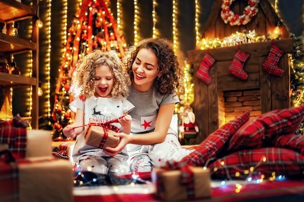 Vrolijk schattig klein meisje en haar oudere zus die geschenken uitwisselen.