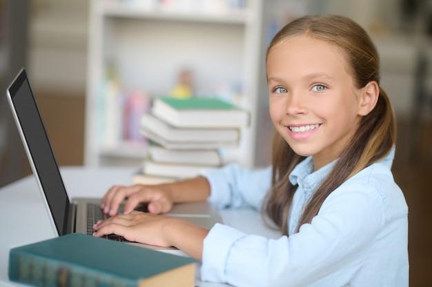 Vrolijk schattig meisje dat op de laptop in de bibliotheek werkt