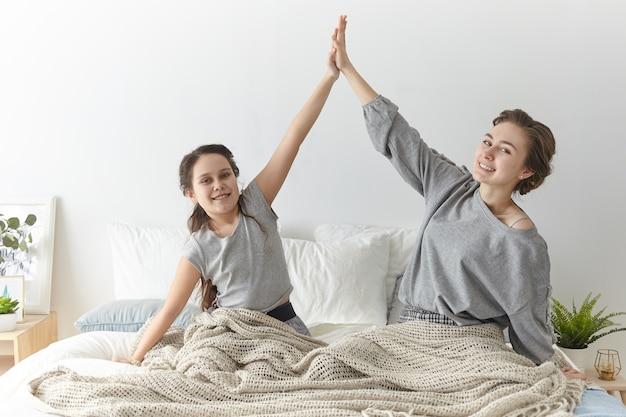 Vrolijk schattig meisje en haar jonge moeder geven elkaar high five in vrijetijdskleding, zittend op bed, groot nieuws vieren