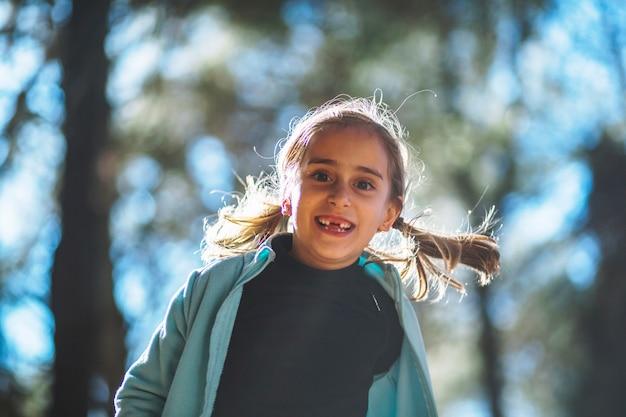 Vrolijk schattig meisje in zonnig bos