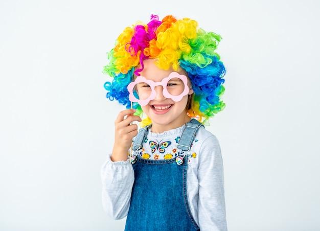 Vrolijk schoolkind in regenboogpruik