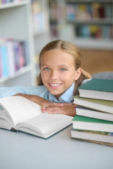 Vrolijk schoolkind poseren voor de camera in een openbare bibliotheek
