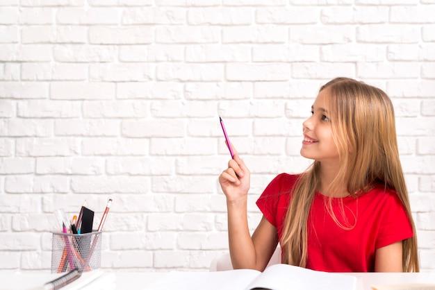 Vrolijk schoolmeisje dat over thuiswerk denkt