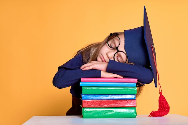 Vrolijk schoolmeisje in afstuderen outfit slepping op stapel handboeken