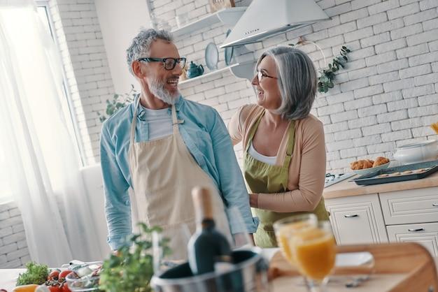 Vrolijk senior koppel bereidt zich voor om een diner te koken en glimlacht terwijl ze thuis tijd doorbrengen