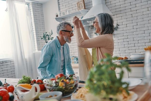 Vrolijk senior koppel bereidt zich voor om een diner te koken en glimlacht terwijl ze thuis tijd doorbrengt