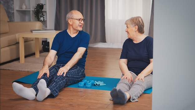 Vrolijk senior koppel doet fysieke training in de woonkamer. oude persoon gezonde levensstijl oefening thuis, training en training, sportactiviteit thuis