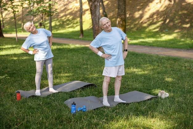 Vrolijk senior koppel in sportkleding doet zijwaartse bochten in stadspark