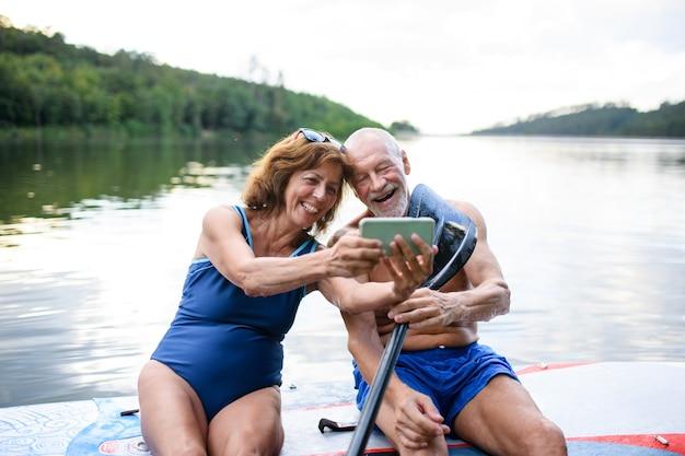 Vrolijk senior koppel zittend op paddleboard op meer in de zomer, selfie nemen met smartphone.