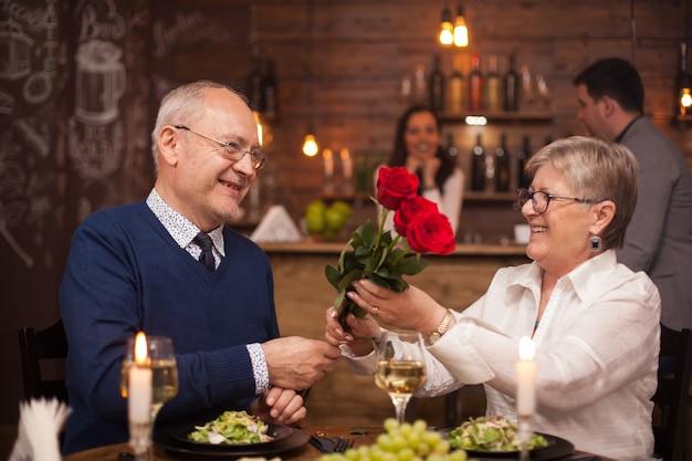 Vrolijk senior paar blij met hun date. echtgenoot die bloem geeft aan zijn vrouw. genieten van pensioen.