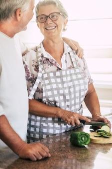Vrolijk senior volwassen stel dat thuis samenwerkt in de keuken en verse seizoensgroenten snijdt, klaar om te koken voor een gezonde lunch