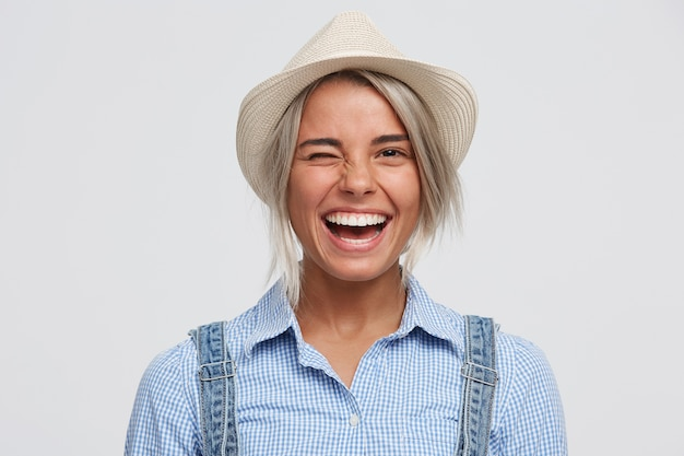 Vrolijk speels gelukkig meisje in een hoed glimlacht en knipoogt in een positieve, vrolijke bui