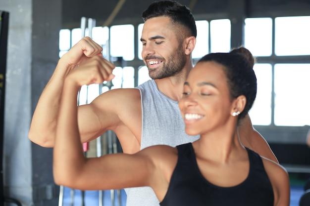 Vrolijk sportief paar dat samen traint en biceps laat zien in de sportschool.