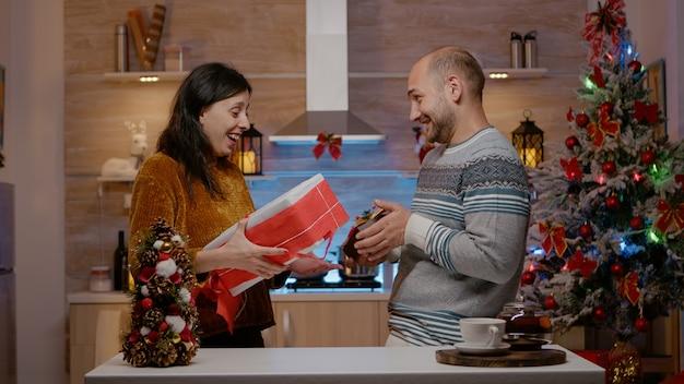 Vrolijk stel dat cadeautjes uitwisselt op kerstavonddag