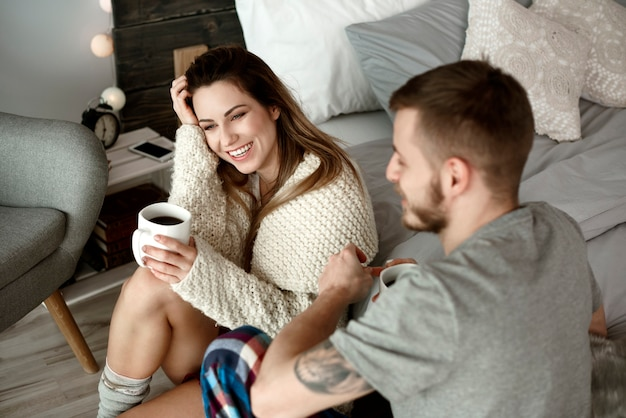 Vrolijk stel met koffie praten en lachen