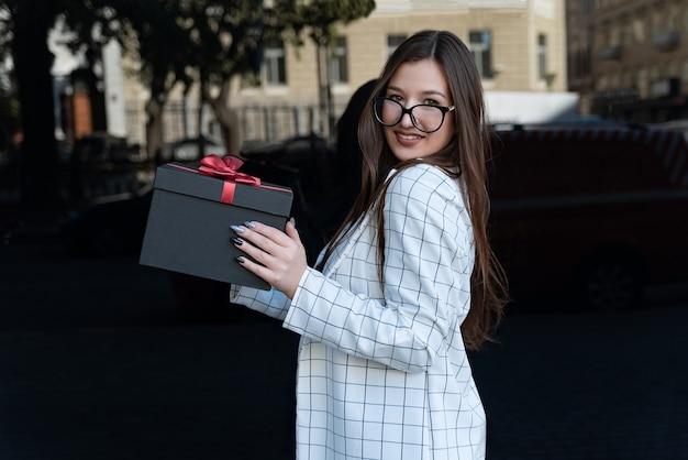 Vrolijk stijlvol meisje in jas en bril houdt zwarte doos met rode strik. gelukkige jonge vrouw houdt geschenkdoos in handen.