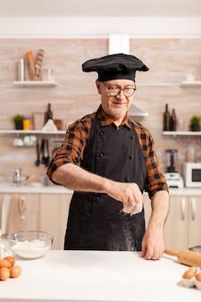 Vrolijk strooit bloem op tafel om deeg te maken voor zelfgebakken brood. gepensioneerde senior chef-kok met bonete en schort, in keukenuniform beregening zeven zeven ingrediënten met de hand.