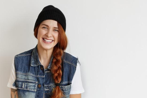 Vrolijk student meisje in stijlvolle kleding binnenshuis ontspannen na de universiteit